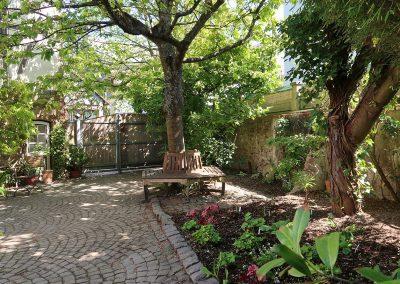 Hoftor, Rundbank unterm Kirschbaum und neu bepflanztes Beet an einem Frühlingsmorgen